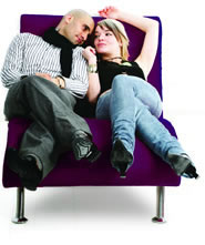Happy young couple lying down on a purple long seat.